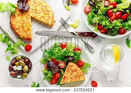 Spanish Tortilla, Omelette With Potato, Onion, Vegetables, Tomatoes, Olives And Herbs In A White Pla
