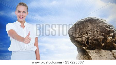 Digital composite of Businesswoman showing thumbs up sign by rock