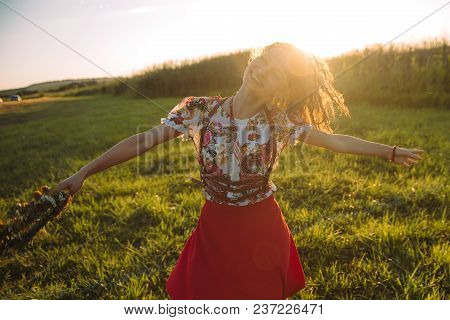 Girl Enjoying Nature On The Field . The Girl Is Joyful Spinning With A Wreath Of Flowers In Her Hand