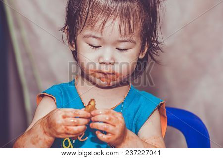 Portrait Of A Asian Child Enjoy Eating. Her Hand And Mouth Get Stained With Ketchup And Dirty. Charm
