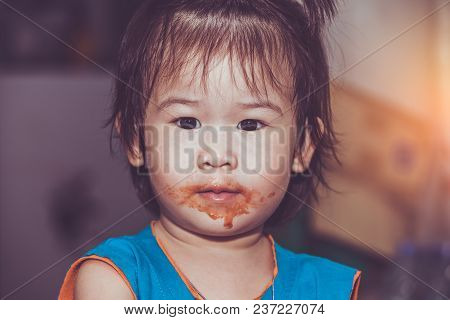 Portrait Of A Asian Child Enjoy Eating. Her Mouth Get Stained With Ketchup. Charming Girl Playing Wi