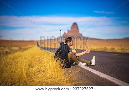 Tired Hitch-hiker With Suitcase Sitting On A Scenic Road In Arizona, With His Thumb Up. Concept Of T