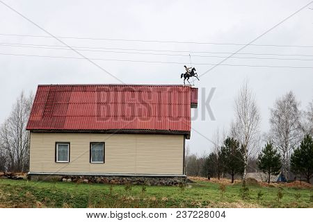 White Country House Trimmed With Siding With Windows And A Red Roof With A Weather Vane In The Form