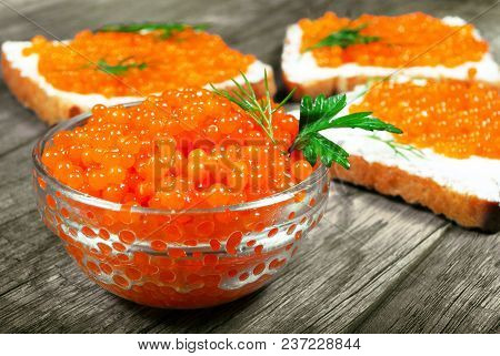 Red Caviar. Red Caviar In A Spoon On A Background Of Toasts With Red Caviar. Close-up.