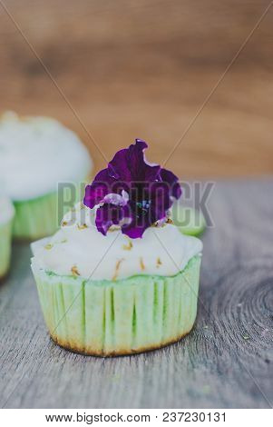Cupcake Decorated With Meringue And Violet Flower And Lime Peel, Selective Focus