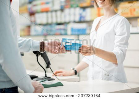 Pharmacist Giving A Box With Medication For The Client In Pharmacist. Close-up View Focused On The H