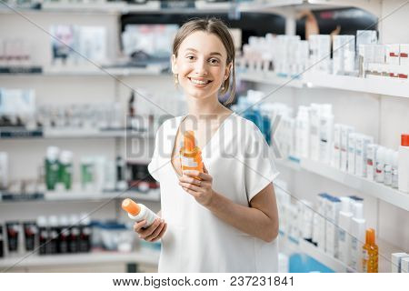 Young Woman Customer Choosing Sunscreen Lotion At The Pharmacy Store