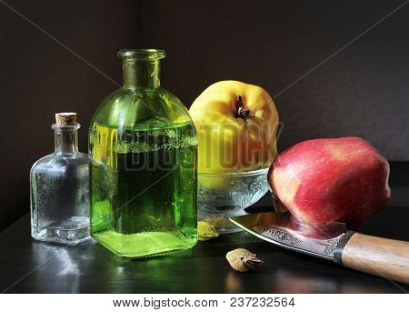 Still Life With Ripe Yellow Quince, Red Apple And Two Vintage Glass Bottles Against A Low Key Backgr