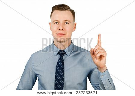 Young Businessman Dressed In Blue Shirt And Tie Shows Index Finger Up, Isolated On White Background