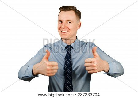 Young Businessman Dressed In Blue Shirt And Tie Shows Thumbs Up And Smiles, Isolated On White Backgr