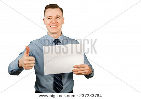 Young Businessman Dressed In Blue Shirt And Tie Holding Blank Blank Sheet Of Paper A4 And Shows Thum
