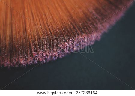Close Up. Blurred Image Of A Brush Smears Grains Of Powder On A Black Background.