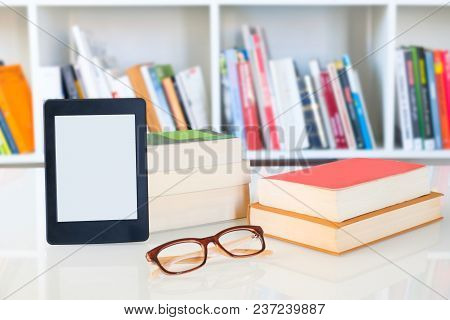 Ebook Reader And Reading Glasses On Bookshelf Background.copy Space On Digital Tablet Display