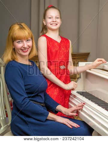A Beautiful Young Mother With A Little Daughter Near A Large White Grand Piano. The Concept Of Famil