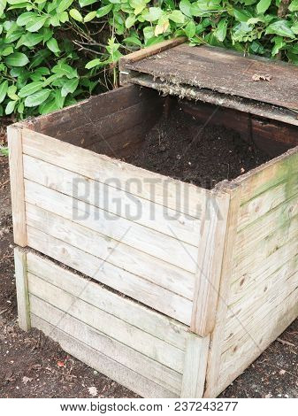 Wood Compost Bin In The Grass Next To Vegetable Garden
