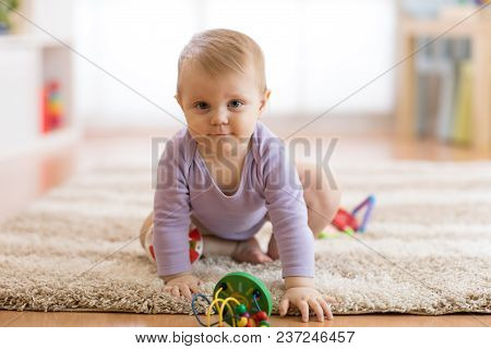 Cute Baby Girl Crawling On The Floor In Nursery Room