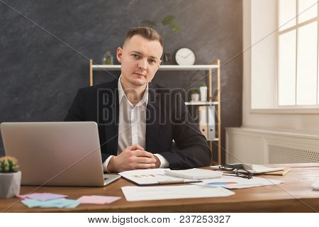 Serious Successful Male Financial Advisor Working With Papers And Laptop At Modern Office. Pensive M