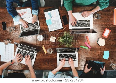 Top View Of Coworking People Sitting Together Around Table. Business Meeting Of Young Creative Hipst