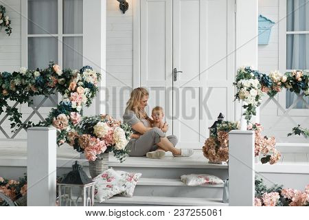 Young Mother Breastfeeding Baby, Sitting On Floor Near Home Porch Outdoor. Happy Woman Holding Her N