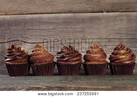 Tasty Chocolate Cupcakes On Grey Wooden Table