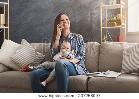 Happy Mother Working At Home Office With Her Baby. Young Woman Talking On Phone While Spending Time