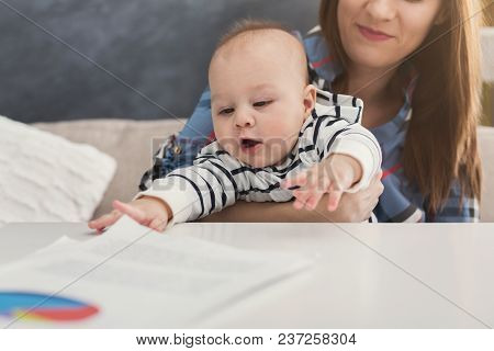 Happy Business Mom Working With Diagrams In Home Office And Her Cute Baby Stretching To Papers. Busi