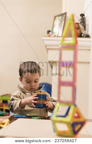 The Boy 2 Years Building A Tower From A Bright And Colorful Designer. Intellectual Toys. The Child P