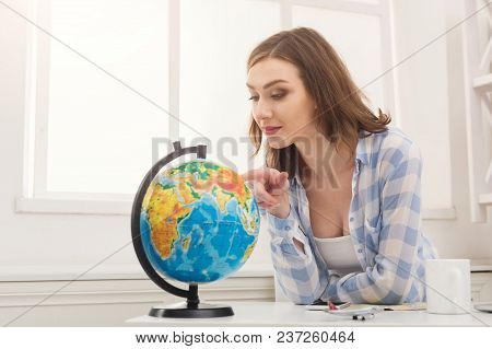 Young Pensive Woman Dreaming About Traveling Around World, Looking At Globe At Home. Pretty Girl Stu