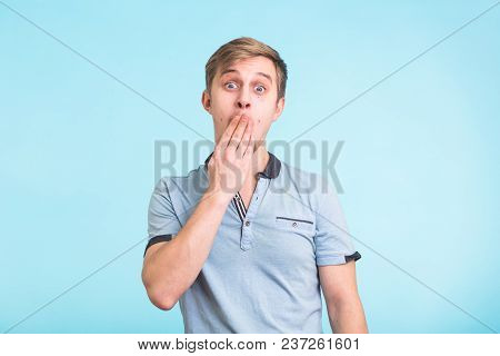 Portrait Of Amazed Man Covering His Mouth Over Blue Background.
