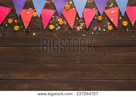 Pink Paper Flags Garland On Rustic Wood. Birthday Party Decoration Background, Top View, Copy Space.
