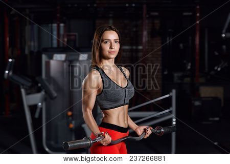 Young Beautiful Sportswoman Doing Exercises In The Gym With A Barbell. Fitness Concept Background.