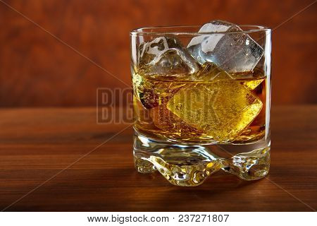 Whiskey On The Rocks On Wooden Table , Red Background