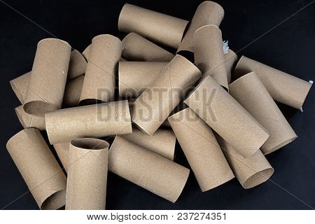 Close Up Of A Pile Of Empty Cardboard Toilet Paper Rolls On Black