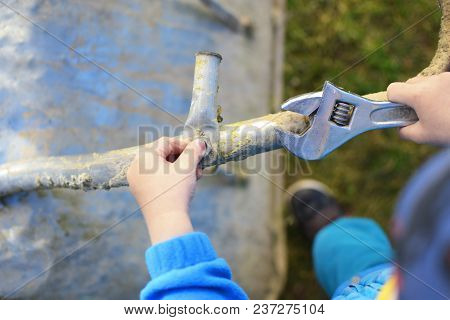 Little Two Years Old Boy Hands Screwing Screw With Wrench Learning To Repair  Wheelbarrow In Grass O