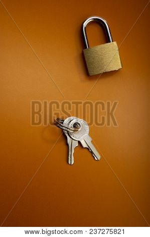 Closed Padlock And Keys Lie On A Dark Background.