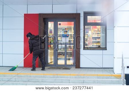 Kamensk-uralsky, Russia, February 10, 2018: Janitor Sweeps The Porch Of The Store