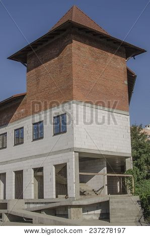 Brick Two-tone Building Under Construction In The Form Of A Tower.