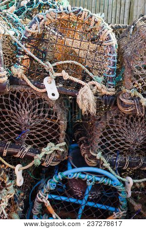 Lobster And Crab Pots Or Traps Stacked On A Harbour Wall Used For Catching Shell Fish And Crustacean