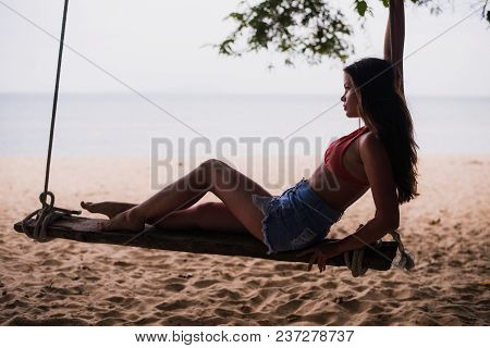 Traveler Woman Relaxing On Wooden Swing. Young Fashion Woman Relax On The Beach. Happy Island Lifest