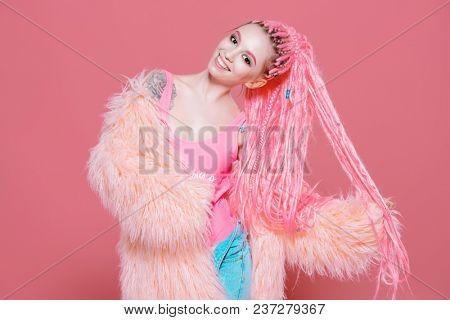 Stylish girl with pink dreadlocks posing in bright clothes on a pink background. Beauty, fashion.
