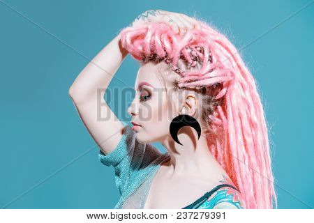 Stunning female model with pink dreadlocks posing on a gray background. Trendy hairstyles. Beauty, fashion.