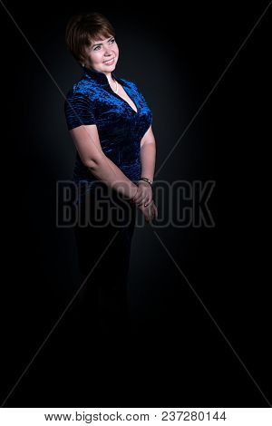 Full-length Portrait Of A Middle-aged Woman On A Black Background