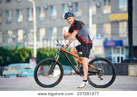 Sporty Smiling Guy Biker In Cycling Clothes And Helmet On Bicycle, Looking To The Camera, Showing Th