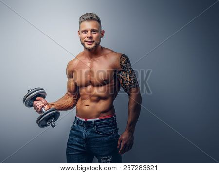 A Handsome Shirtless Bodybuilder With Stylish Haircut And Beard, With Tattoo On His Arm, Posing With