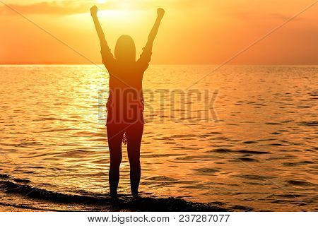 Silhouette Of Happy Woman Celebrated Success With Arm Up At The Beach During Sunset