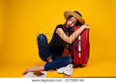 A Young Girl In A Hat Is Sleeping On A Big Red Suitcase, Waiting For Her Plane, Going On Vacation