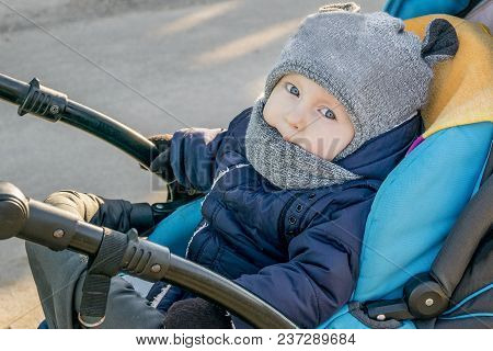 Little Boy Sitting In A Baby Carriage On The Street. Kid Dressed In Warm Clothes