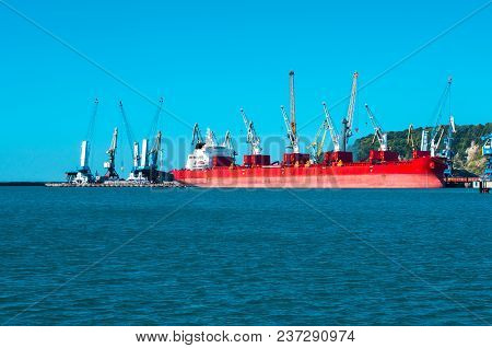 Big Red Ship On A Shipyard Industrial Background