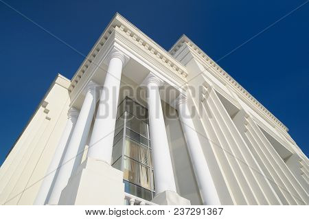 Classic Style White Building Facade Detail With Pillars Against Clear Blue Sky. Modern Architecture.