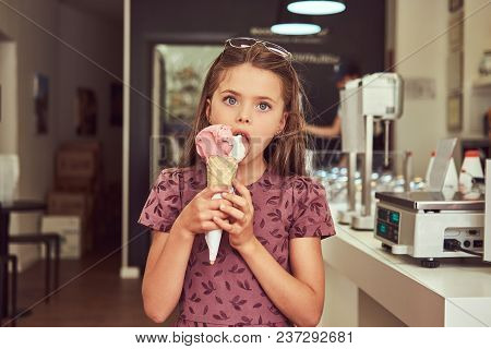A Beauty Little Girl In A Fashionable Dress Eating Strawberry, Standing In An Ice Cream Parlor.